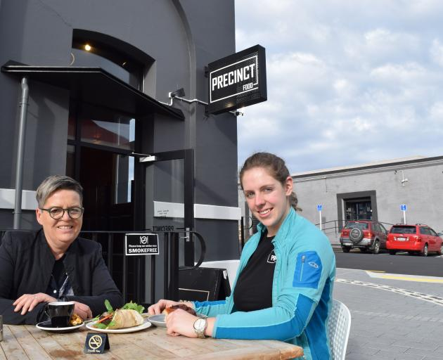 Precinct Food owner Liz Christensen (left) and chef Louise Evans eat lunch in the smokefree outdoor dining area of the eatery in Dunedin's warehouse precinct. Photo: Shawn McAvinue