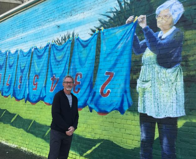 Artist Bill Scott stands next to his recently created mural of Waimate Rugby Club stalwart the late Stella Chamberlain. Photo: Chris Tobin