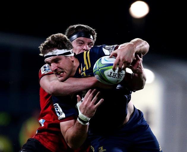 Luke Whitelock, of the Highlanders, is tackled by Crusader Scott Barrett during their Super Rugby...