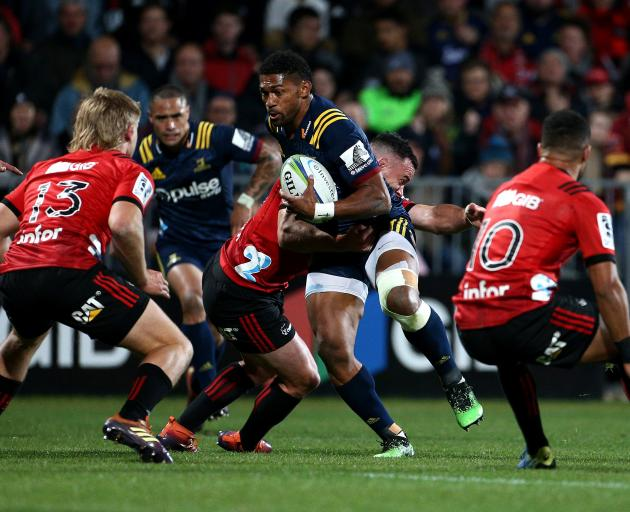 Winger Waisake Naholo does his best to break out of  the tackle of Crusader Ryan Crotty. PHOTO:...