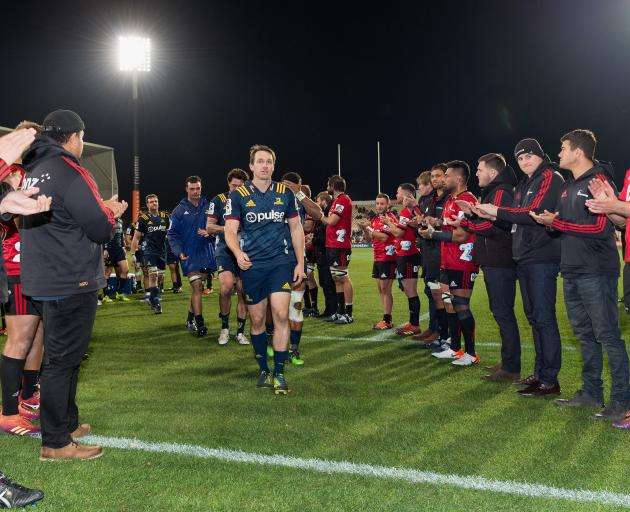 Highlanders great Ben Smith gets a guard of honour from Crusaders players following last night's...