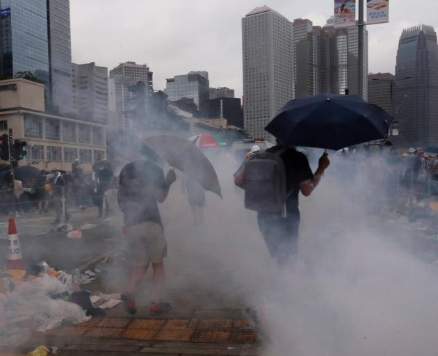 Protesters react to tear gas during a demonstration against a proposed extradition bill in Hong...