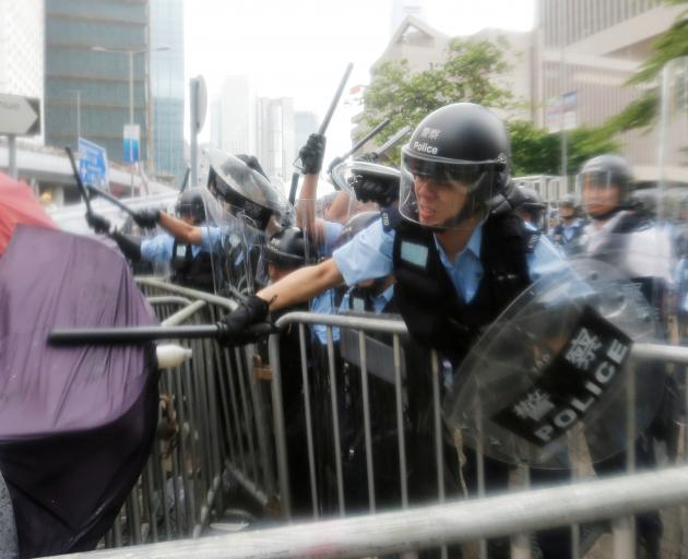 Police use batons on protesters demonstrating against a proposed extradition law to China in Hong...