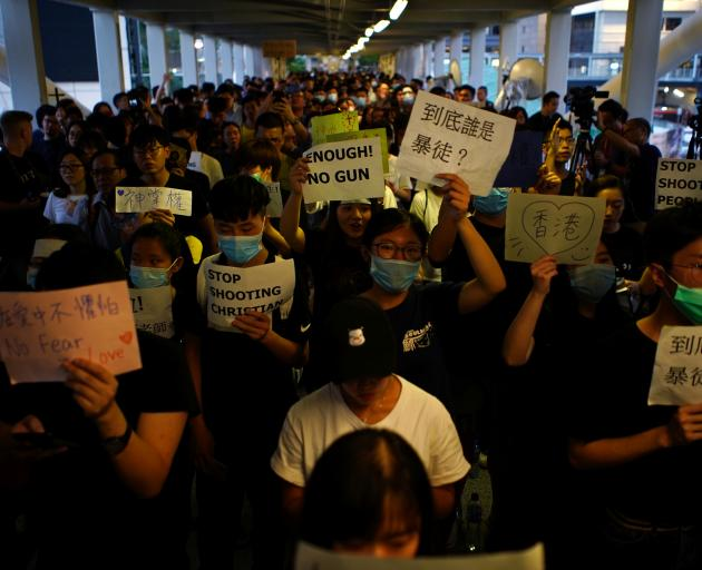 Protesters hold signs following a day of violence over the proposed extradition bill. Photo:...