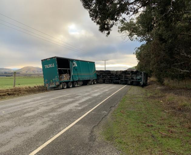 A Toll truck lies overturned on State Highway 8 near Tarras yesterday. The road was blocked for...