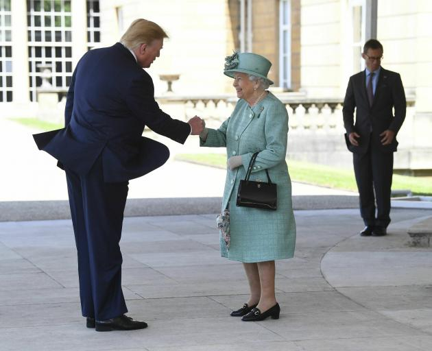 The Queen greets Donald Trump as he arrives for a welcome ceremony in the garden of Buckingham...