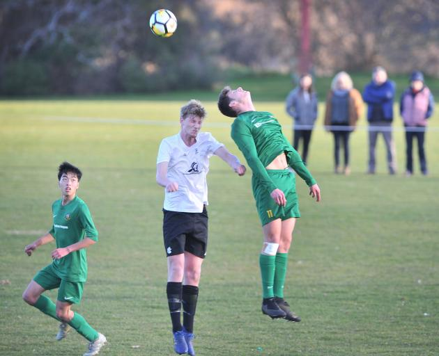 Green Island's Matt Brazier (right) heads the ball as Roslyn-Wakari's Josh Lucas competes and...