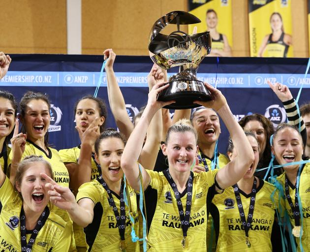 Pulse captain Katrina Rore holds the ANZ Premiership trophy aloft in front of her team-mates...