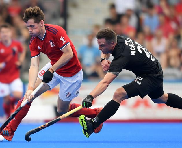 Shea McAleese, of the men's Black Sticks, is at full stretch trying to contain Great Britain's...