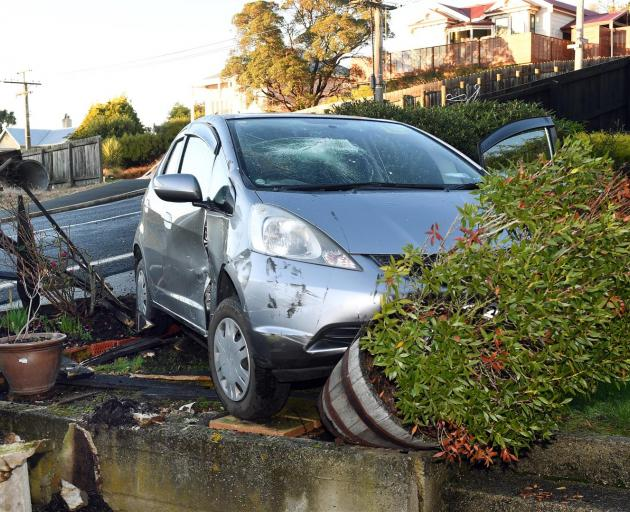 A car sits in the garden of Dave and Vanya Hammond's home in Mornington yesterday after it crashed through the fence, narrowly missing their caravan, in the latest of a spate of crashes into their yard. Photo: Stephen Jaquiery