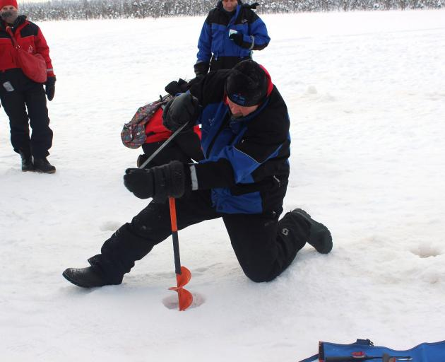 Guide Marrku uses an auger to break through the ice on the frozen  Pikku-Mellalampi Lake.
