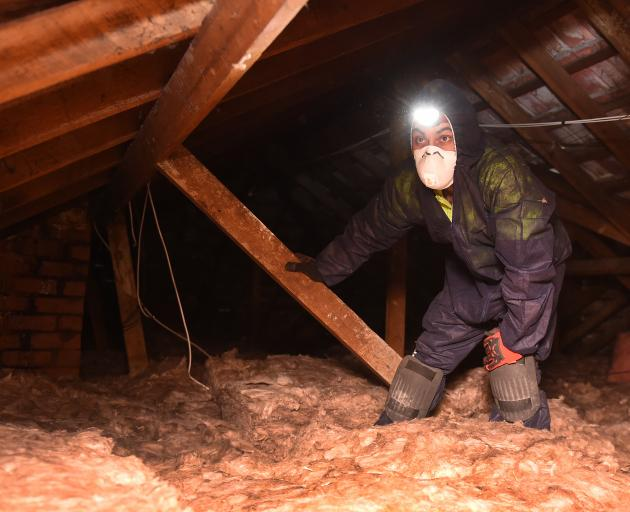 WarmUp Solutions installer Muhammad Hassen (22) installs insulation at a Russell St property, in...