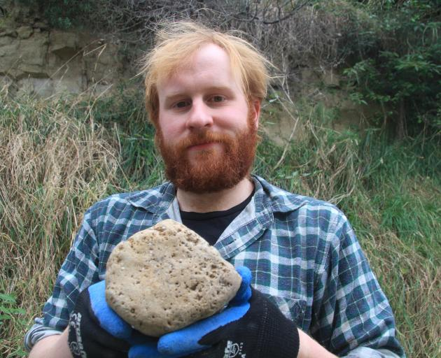 """Assistant research fellow Marcus Richards shows the telltale """"honeycomb'' in a fossilised whale..."""