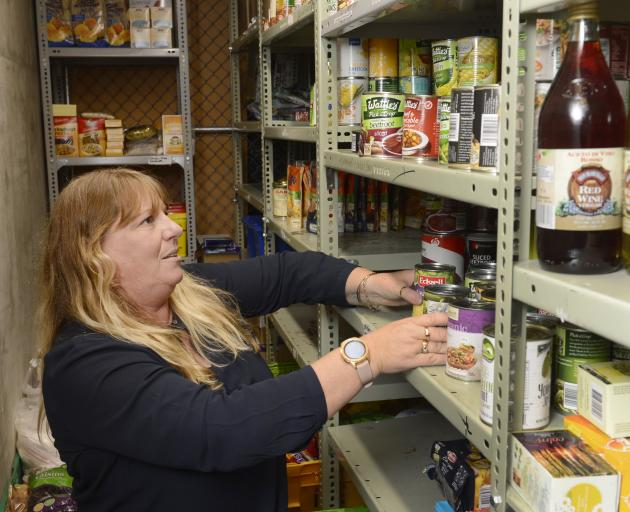 Practice manager Deb Gelling makes room on the shelves of Presbyterian Support Otago's food bank...