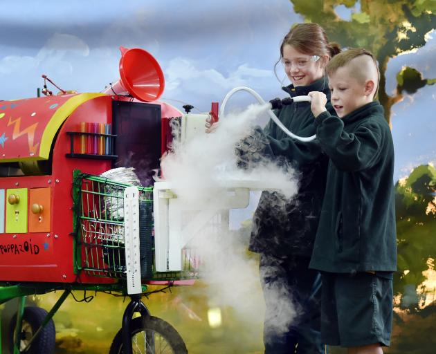 Green Island School pupils Willow Kenny and Tristen Pickering (both 9) play with the Poppazoid during its visit to the school yesterday. Photo: Peter McIntosh