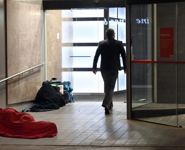 Fast asleep, wrapped tightly in blankets in the entrance to the Westpac building in George St, Dunedin, on the coldest morning of the year yesterday are two rough sleepers. Photo: Stephen Jaquiery