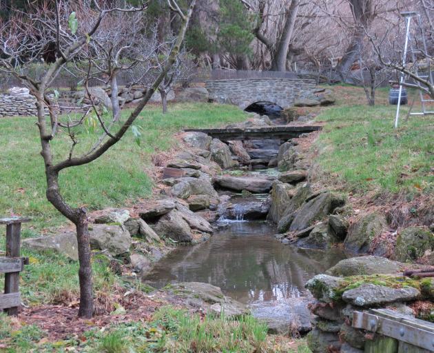 A stonework bridge spans a creek in Jane Falconer's Clachanburn gardens, in Maniototo.