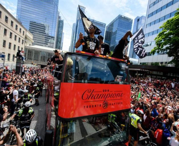 The Toronto Raptors make their way through the crowded streets of Toronto at their NBA...