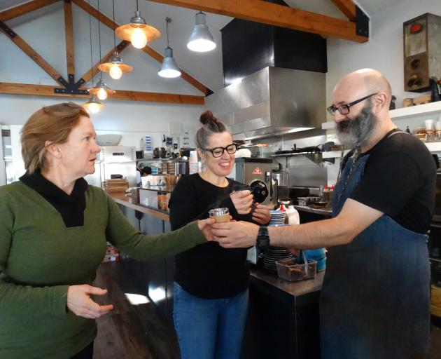 Plastic Free Wanaka's Sophie Ward (left) and Federal Diner owner Brona Parsons taste-test a takeaway coffee made by barista Robert Holt in a reusable cup. Photo: Kerrie Waterworth