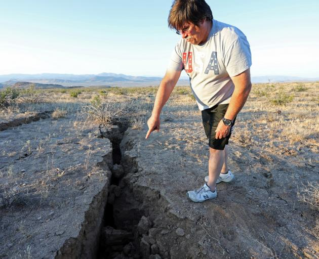 A man looks into a fissure that opened in the desert during a powerful earthquake that struck...