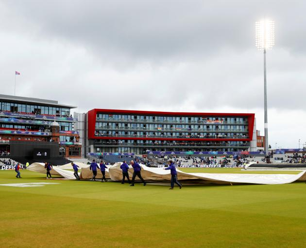 The covers came off and on during a four hour wait in vain for the game to resume, Photo: Reuters