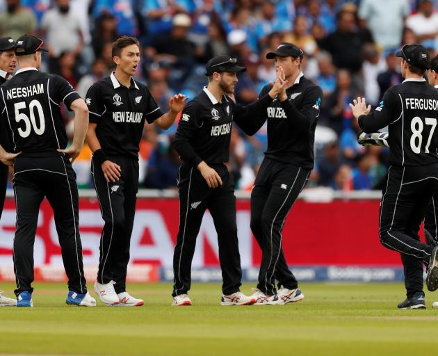 New Zealand's Kane Williamson celebrates with Trent Boult and team mates after taking a catch to...