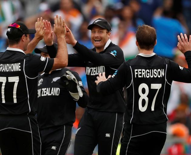 New Zealand's Martin Guptill celebrates with team mates after taking the wicket of India's MS...