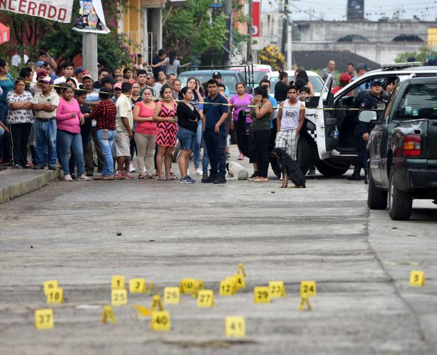 People stand near bullet casings on the ground at a crime scene after a shootout in the municipality Tuzamapan. Photo: Reuters