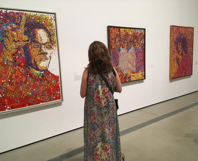 A woman examine's Wadsworth Jarrell's 'Black Prince', a portrait of Malcolm X, and other Jarrell...