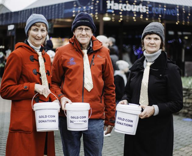 Volunteers (from left) Sue Iveson, Bill Iveson and Sharon Smidall collect donations for next year...