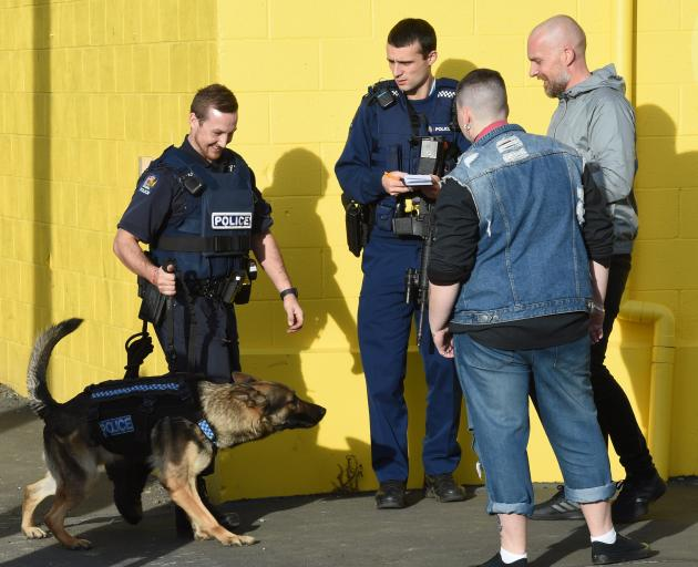 An officer takes a statement from a witness as Dunedin dog-handler Constable Regan Wilson and his...