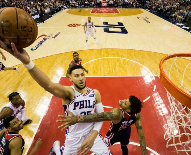 Ben Simmons lays the ball up for the Philadelphia 76ers past the Washington Wizards' Kelly Oubre....