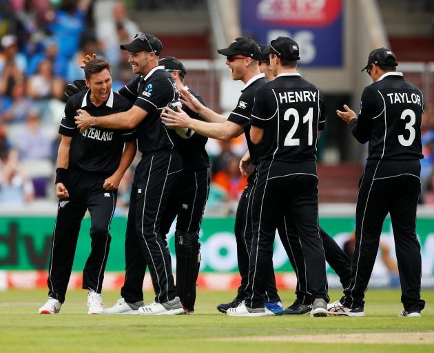 Trent Boult celebrates with team mates after taking the wicket of India's Virat Kohli. Photo:...