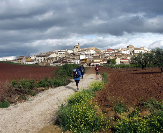 Camino de Santiago pilgrims approach a small Spanish town in search of breakfast after an early...