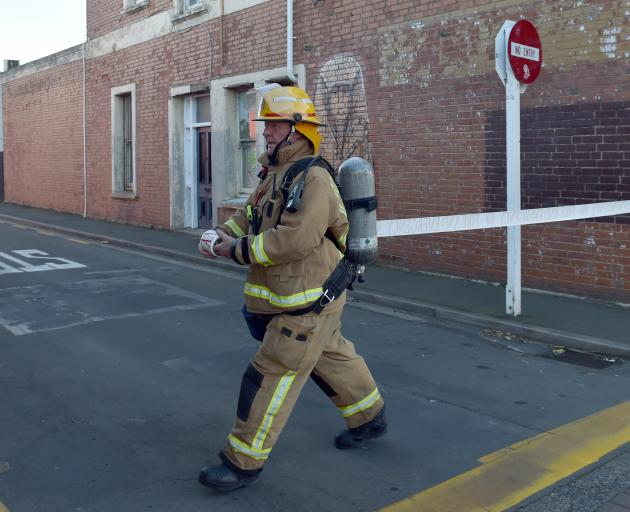 A firefighter cordons off Sullivan Ave between King Edward St and Glasgow St during a chemical...