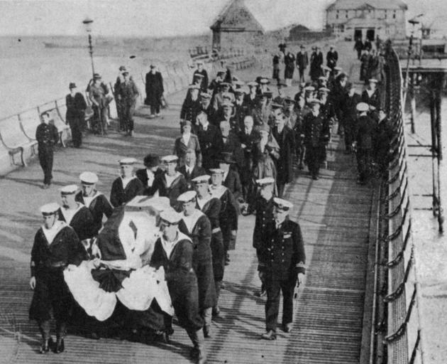 Bluejackets carry the casket containing the body of the martyred nurse, Edith Cavell, from the wharf at Dover. Immediately behind the casket are (from left): Miss Scott Cavell (sister), Dr Wainwright (brother-in-law) and Mrs Wainwright (sister). - Otago W