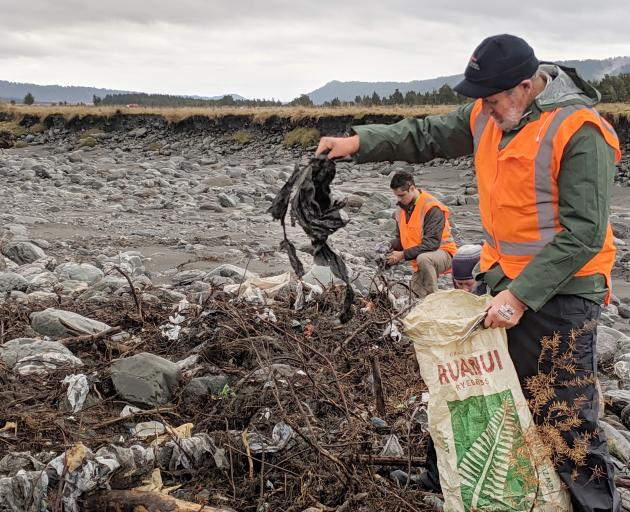 Aucklander John Duder travelled to the West Coast to volunteer cleaning up on the Fox River after his teenage grandson saw the story on the news and asked his granddad if they could help. Photo: DOC