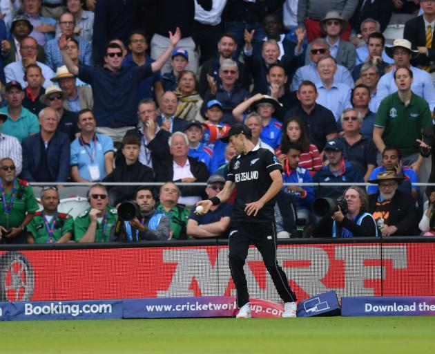 Trent Boult of New Zealand treads on the boundary after taking a catch from Ben Stokes. Photo:...