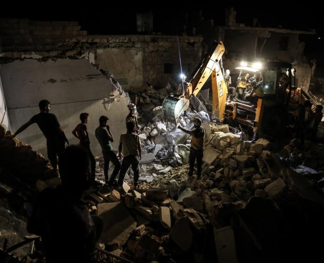 Rescue personal search for survivors in the rubble of a recently bombed building in Idlib...
