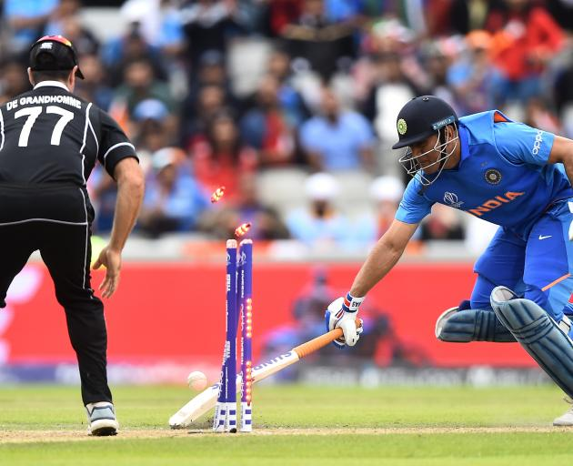 Black Caps all-rounder Colin de Grandhomme watches on as Indian wicketkeeper-batsman MS Dhoni is...
