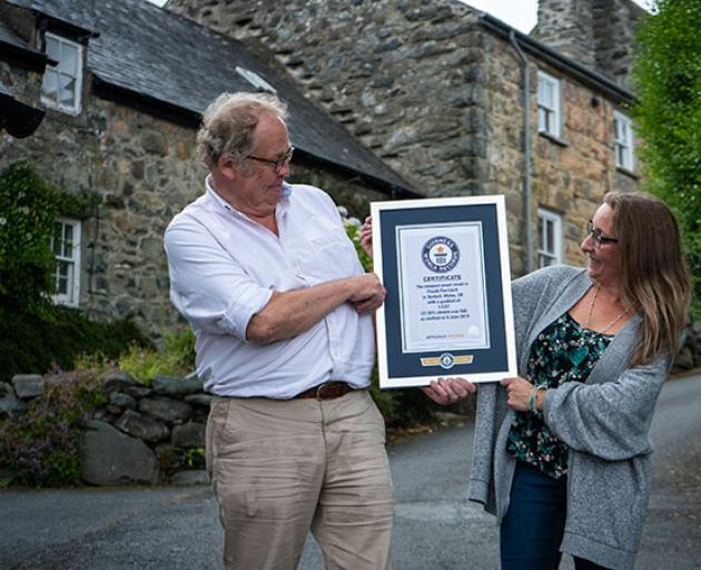 Harlech residents Gwyn Headley and Sarah Badham admire the certificate from the Guinness World Records officially recognising their street Ffordd Pen Llech as the world's steepest. Photo: Supplied