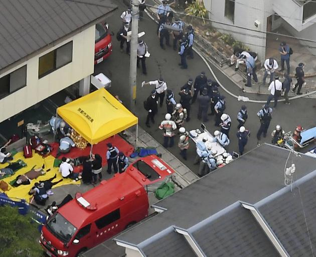 Rescue workers carry injured people from the three-story Kyoto Animation building which was torched in Kyoto. Photo: Kyodo/via Reuters