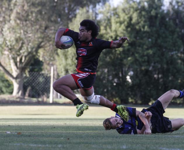 Old Boys player Suli Tuivailalal powers through the attempted tackle of Excelsior's Tarn Crow in...