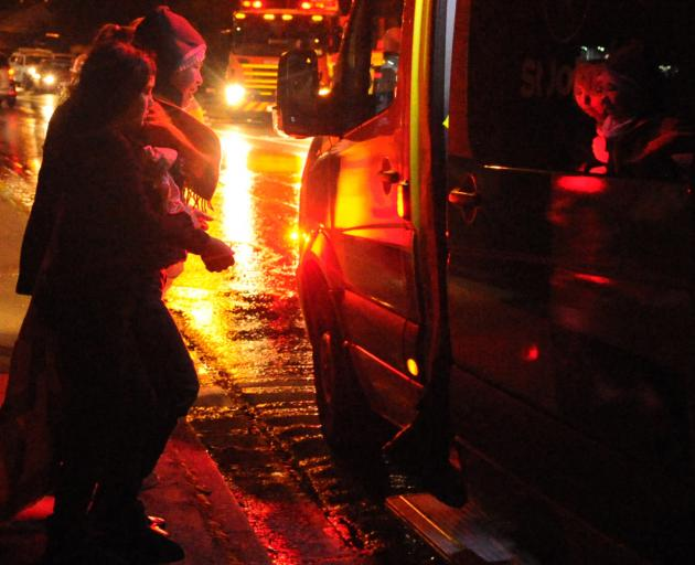 The mother and daughter inside the restaurant when the fire began are helped to a St John ambulance.