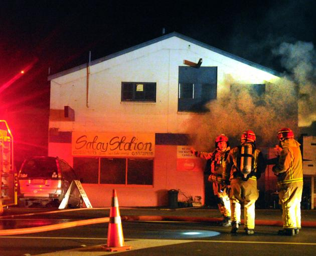 Smoke billows from the Satay Station restaurant in Kaikorai Valley Rd in Dunedin last night as fire rips through the two-storey building. Photo: Christine O'Connor