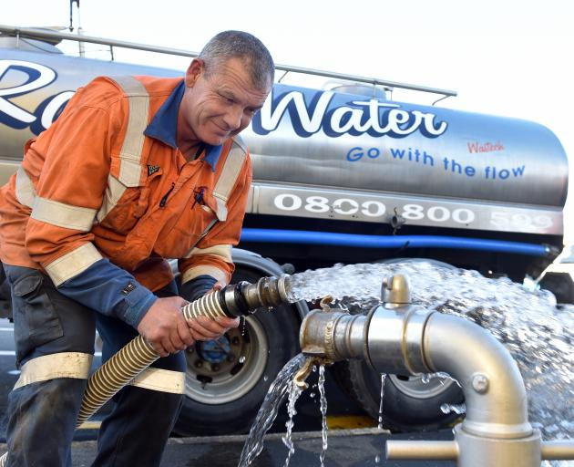 Wastech Services Dunedin employee Greg Hill prepares for another delivery of water yesterday....