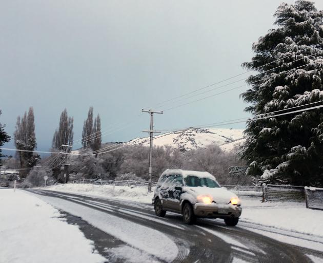 A car heads along a snowy Teviot Rd in Millers Flat on Monday morning. Photo: Supplied