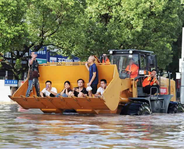 Rescue workers evacuate stranded residents with a bulldozer on a flooded street after typhoon...