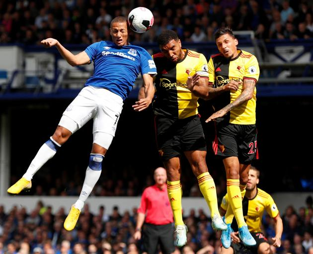 Everton's Richarlison rises high to win a header against Watford's Troy Deeney and Jose Holebas....
