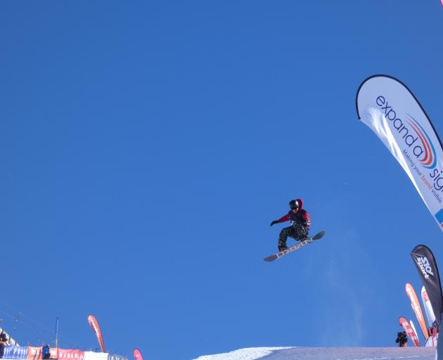 Kiwi snowboarder Rakai Tait glides through the air during yesterday's halfpipe finals at Cardrona. Photo: Adam Burns